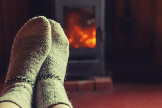 Pés pernas em roupas de inverno meias de lã na lareira