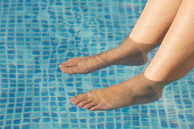 Pés refrescantes na piscina no verão