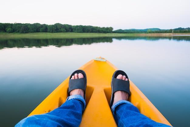 Pés relaxantes em caiaque laranja flutuando no rio e no outono