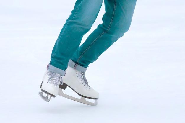 Pés rolando em patins de mulher na pista de gelo. esportes e férias de inverno