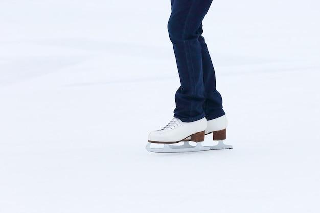 Pés rolando em patins de mulher na pista de gelo