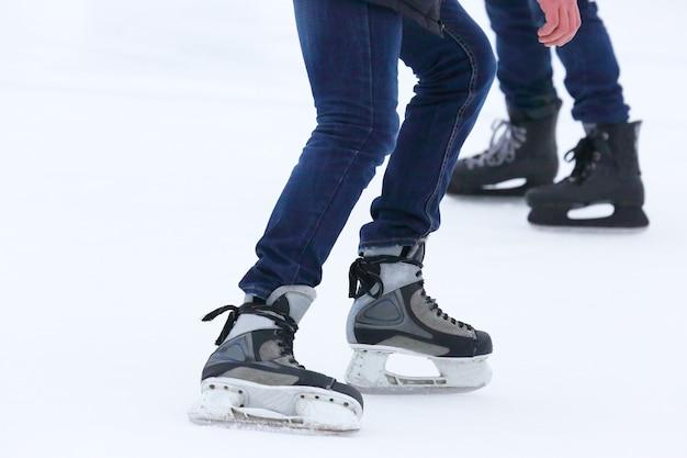 Pés rolando em patins homem na pista de gelo