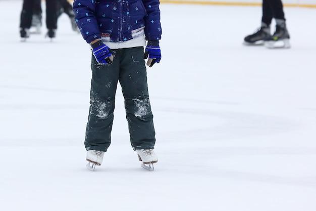 Pés rolando em patins pessoas na pista de gelo