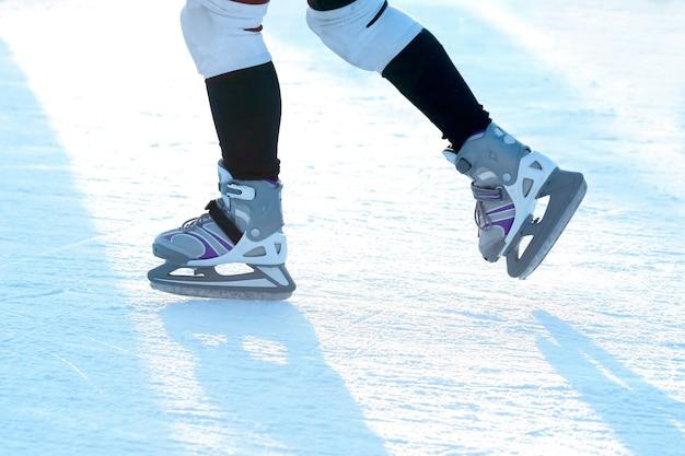 Pés rolando no homem de patins na pista de gelo. esportes, hobbies e recreação de pessoas ativas