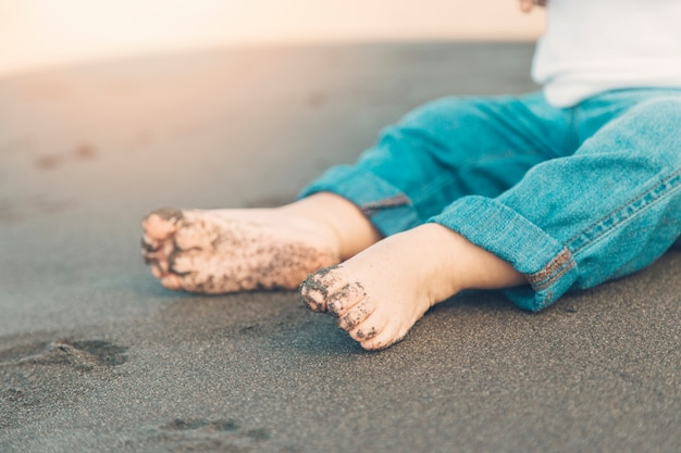 Pés sem sapatos de bebê sentado na areia
