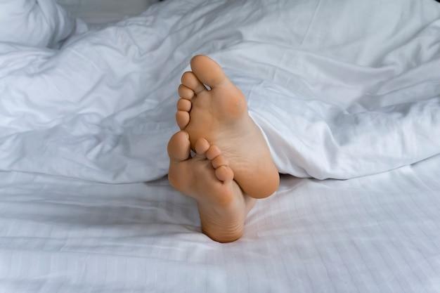 Pés sob as cobertas na cama pela manhã Foto Premium