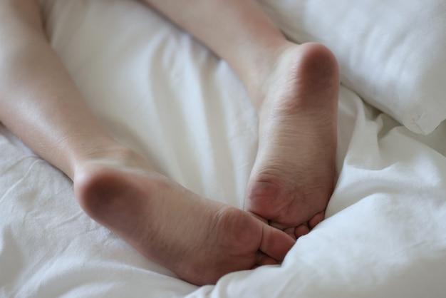Pés sujos de homem deitado na cama branca e limpa