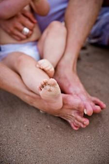 Pés sujos do bebê com areia da praia, após o jogo com as ondas e o mar no verão.