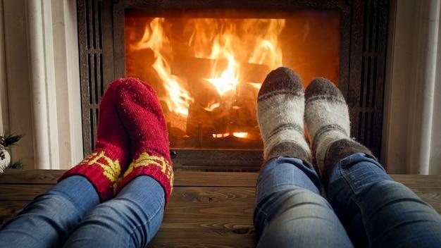 Pés usando meias de malha de lã aquecendo pelo fogo aceso na lareira