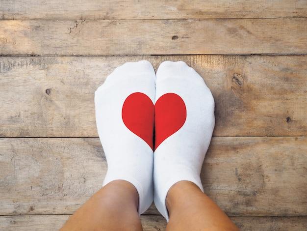 Pés vestindo meias brancas com forma de coração vermelho