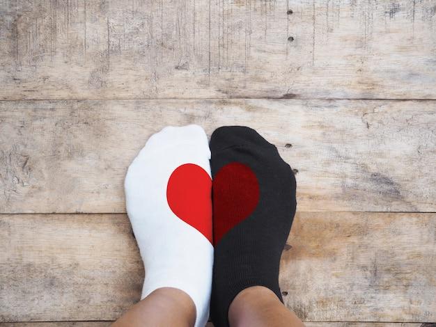 Pés vestindo meias brancas e pretas com forma de coração vermelho