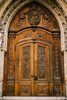 Pesadas portas de madeira com desenhos de figuras esculpidas e símbolos sob um arco com muitas figuras antigas
