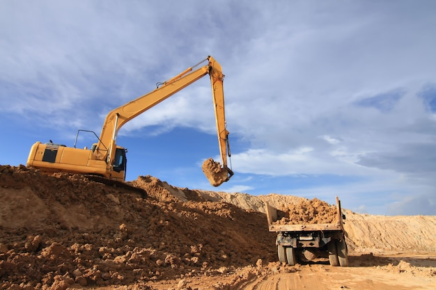 Pesado, escavador, carregando, caminhão basculante, com, areia, em, pedreira, sobre, céu azul
