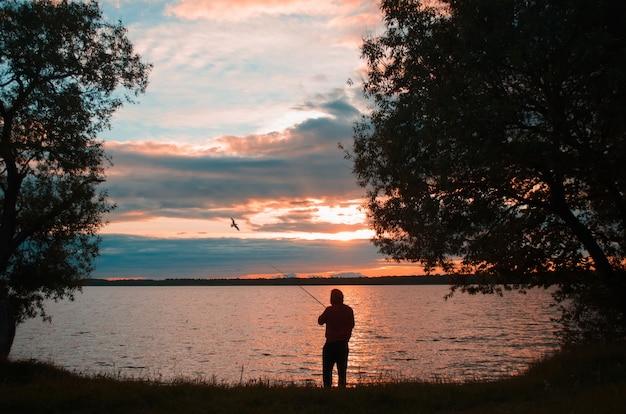 Pesca ao pôr do sol no lago. pescador joga uma vara de pescar, vista traseira. paisagem do sol no lago e uma gaivota voando.