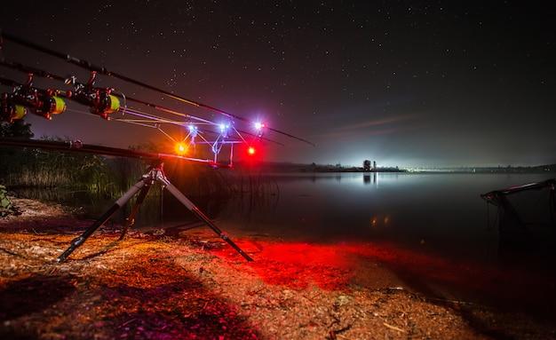 Pesca da carpa que dobram no lago na noite com alarmes iluminados.