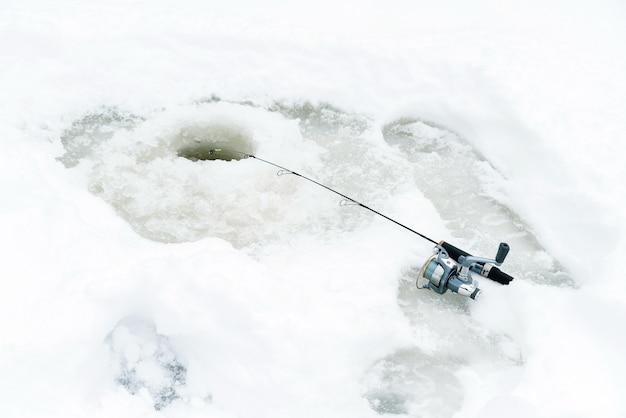 Pesca de inverno no gelo, balançando a isca em um buraco no gelo.