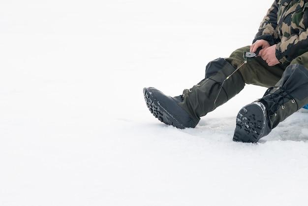 Pesca de inverno no gelo. homem balançando a isca em um buraco no gelo.