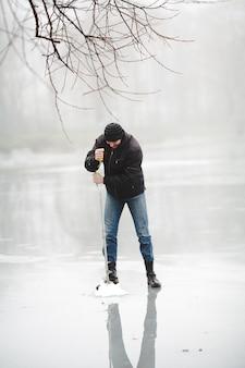 Pesca de inverno no lago congelado com broca de mão