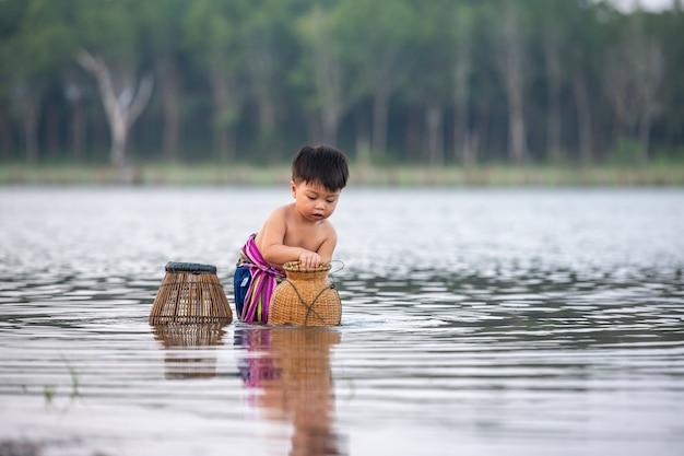 Pesca do menino da pesca no rio pesca do menino pequeno no campo rive de ásia.