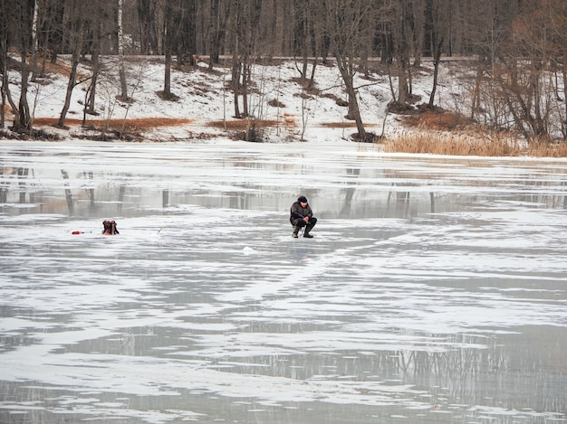 Pesca perigosa no gelo úmido da primavera. pescador no derretimento do gelo úmido. rússia.