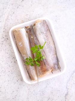 Pescada de peixe cru em embalagem branca decorada com salsa