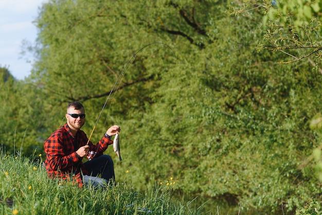 Pescador à beira do rio com pescaria