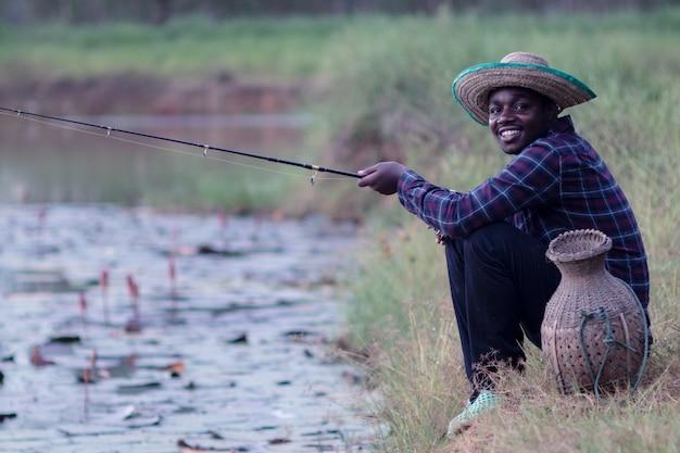 Pescador africano felizmente pega uma vara perto de um lago em uma área rural.
