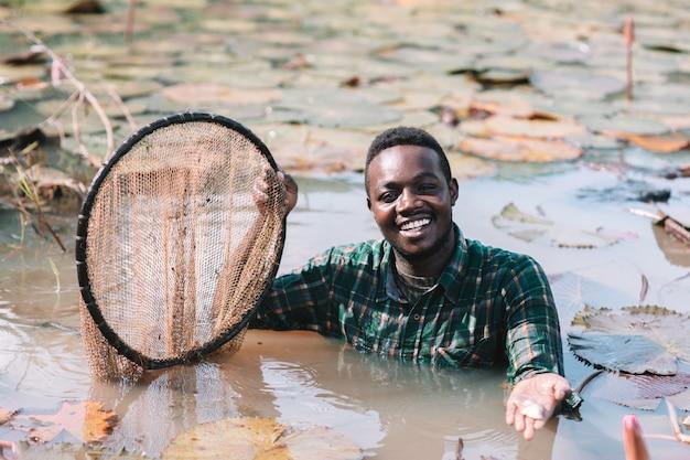 Pescador africano, sorrindo no lago de lótus de flores