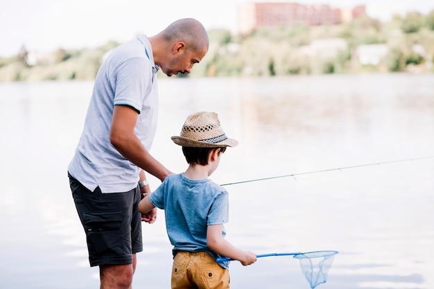 Pescador, ajudando, seu, filho, enquanto, pesca, perto, lago
