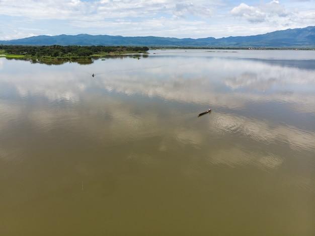 Pescador asiático captura de peixes no lago natural
