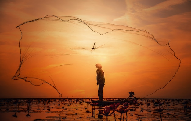 Pescador asiático no barco de pesca no lago