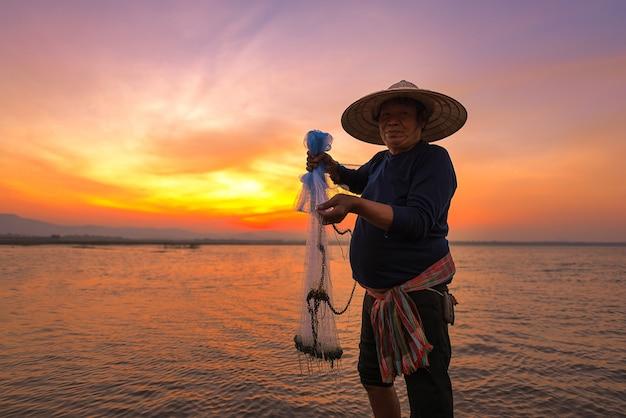 Pescador asiático no rio natureza no início da manhã antes do amanhecer
