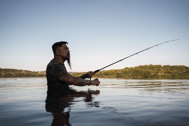 Pescador asiático pescando na margem do rio.