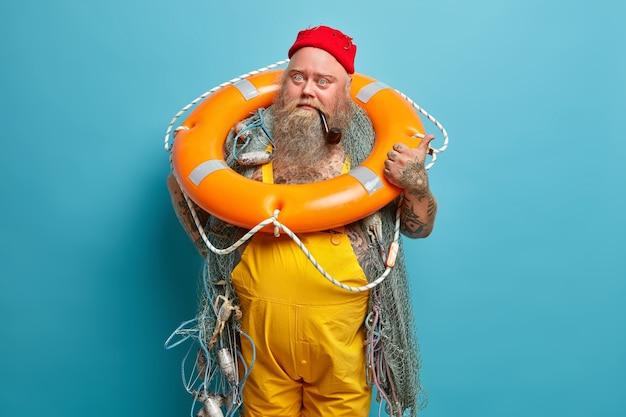 Pescador barbudo experiente e robusto fuma cachimbo com anel inflado e redes de pesca