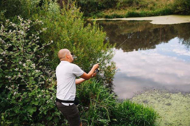 Pescador careca pesca no lago ao ar livre