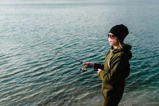 Pescador com molinete na margem do lago
