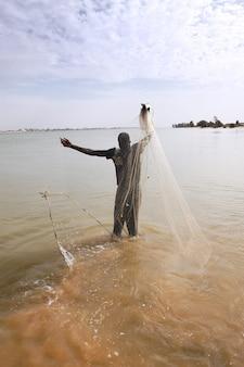 Pescador com rede no rio