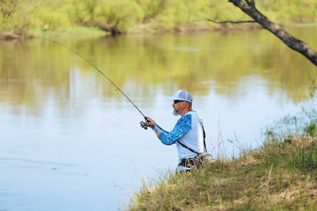 Pescador, com, um, girar, vara, pegando peixe, ligado, um, rio