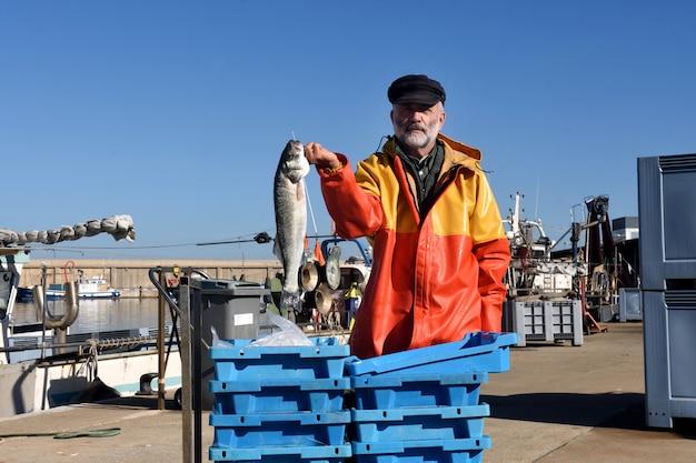 Pescador com uma caixa de peixe dentro de um barco de pesca