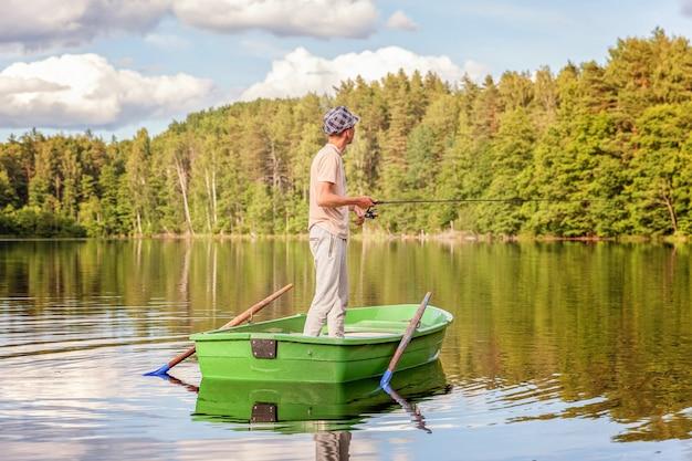 Pescador com vara de pescar está pescando em um barco de madeira no lago ou rio