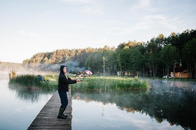 Pescador com vara de pescar na ponte