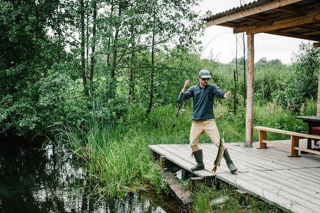 Pescador com vara de pescar pegou um peixe grande pique fora d'água no cais. peixe troféu. dia de pesca.