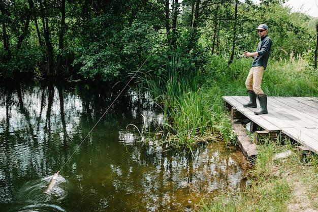 Pescador com vara de pescar pegou um peixe grande pique fora da água na ponte, cais. boa pegada. peixe troféu.