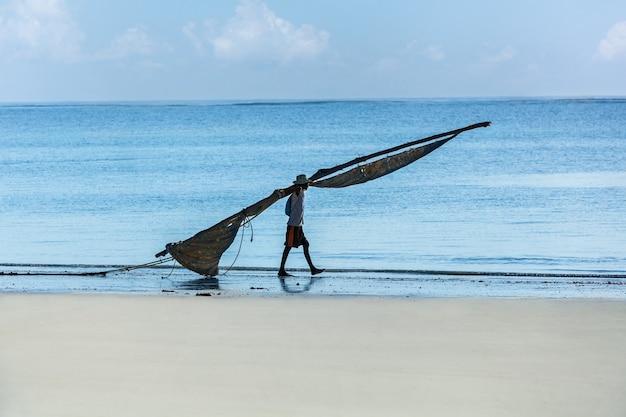 Pescador da áfrica mombaça caminhando na praia com uma vela para um barco,