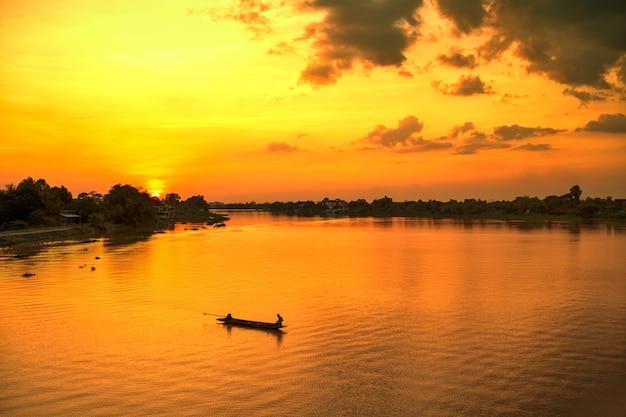 Pescador da silhueta no por do sol do rio do barco.