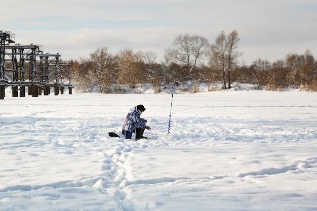 Pescador de gelo em lago de inverno