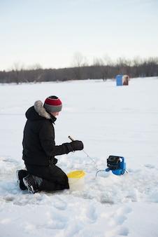 Pescador de gelo pescando em paisagem de neve