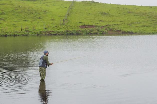 Pescador de robalo pescando dentro do lago
