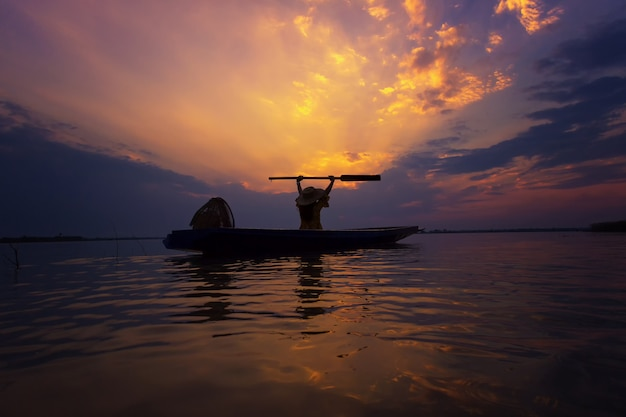 Pescador de silhueta com pôr do sol