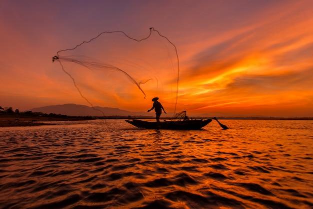 Pescador de silhueta com rede no lago na tailândia